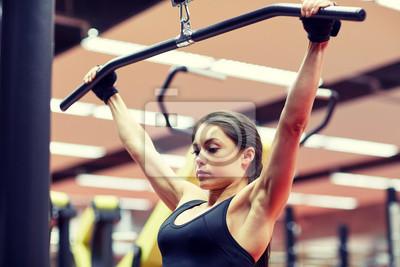 Frau biegt Arm Muskeln auf Kabel-Maschine in der Turnhalle