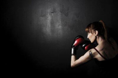 Bild Frau Boxer mit roten Handschuhen auf schwarzem Hintergrund, hoher Kontrast mit entsättigten Grunge-Filter im Studio