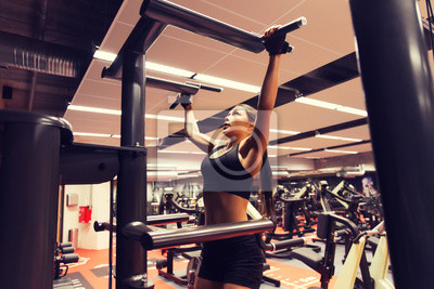 Frau, die trainiert und Pull-ups im Fitnessstudio macht