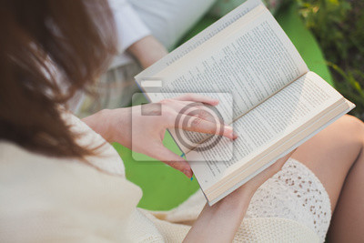 Frau Hand hält ein offenes Buch. Frau liest.