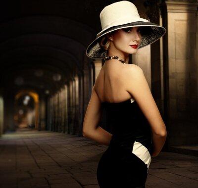 Bild Frau im schwarzen Kleid und großen weißen Hut allein nachts im Freien