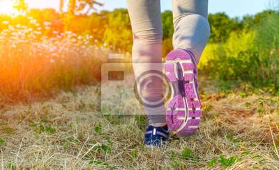Frau läuft bei Sonnenuntergang in einem Feld