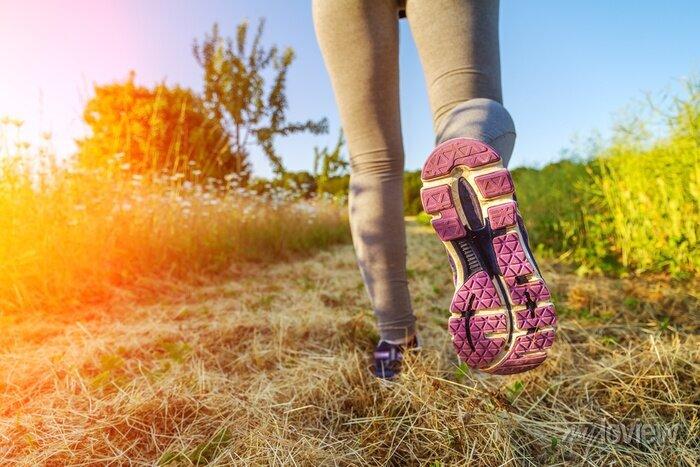 Bild Frau läuft bei Sonnenuntergang in einem Feld