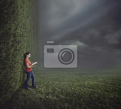 Frau liest auf surreale Landschaft.