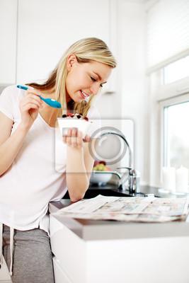 Frau liest die Nachrichten beim Frühstück