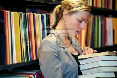 Frau liest in einer Bibliothek