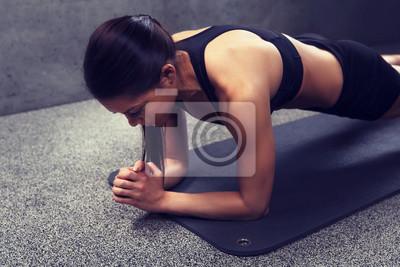 Frau macht Planke Übung auf Matte im Fitnessstudio