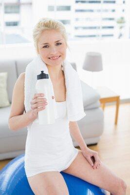 Frau mit der Wasserflasche, die auf Übungsball sitzt