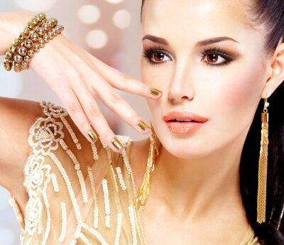 Bild Frau mit goldenen Nägeln und schönen Goldschmuck