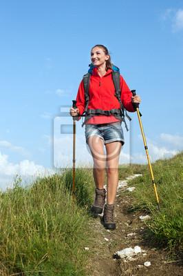 Frau mit Rucksack und Trekkingstöcke