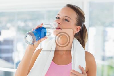 Frau mit Trinkwasser des Tuches in der Turnhalle