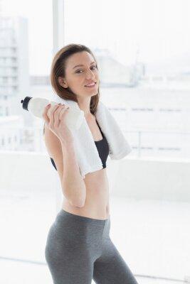 Frau mit Tuch um den Hals, der Wasserflasche im Eignungsstudio hält