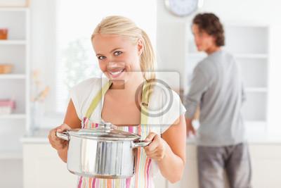 Frau posiert mit einem Kessel, während ihr Verlobter ist das Waschen der dishe