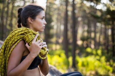 Frau sitzt mit Kletterausrüstung