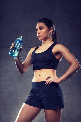 Frau trinkt Wasser aus der Flasche im Fitnessstudio