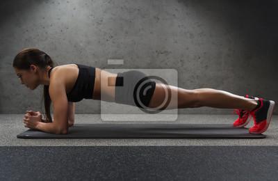 Frau tun Plank Übung auf Matte in der Turnhalle