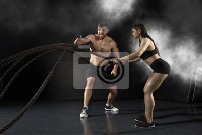 Frau und Männer, die mit Kampfseilen ausarbeiten