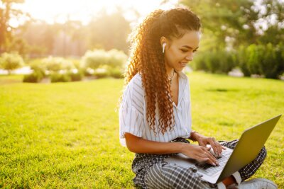 Bild Freelancer woman using laptop computer sitting on grass at park. Young woman working online or studying and learning while using notebook.