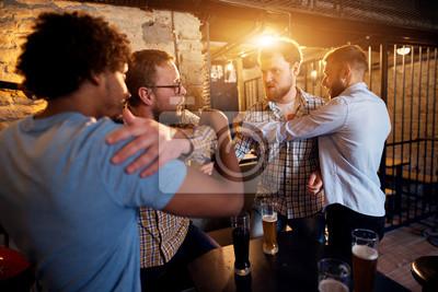 Bild Freunde, die das Kämpfen von zwei verärgerten Kerlen in der Bar verhindern.