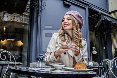 Bild Freundliche französische Frau. Niedrig-winkelige Ansicht von schönen Blondinen im barett weg schauen und beim Sitzen im französischen Weinlesecafé lächeln. Trinkender Kaffee der Frau mit Hörnchen. Fra