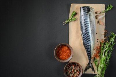 Bild Frische Fischmakrele auf dunklem Hintergrund von oben. Fisch mit aromatischen Kräutern und Gewürzen - gesunde Ernährung, Diät-oder Koch-Konzept
