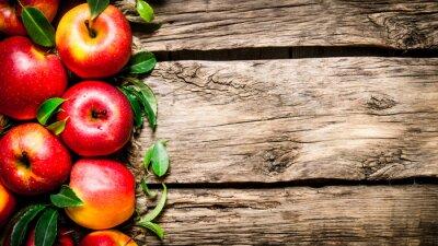 Bild Frische rote Äpfel mit grünen Blättern auf Holztisch.