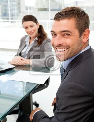 Fröhlich Business-Leute sitzen an einem Tisch mit einem Laptop