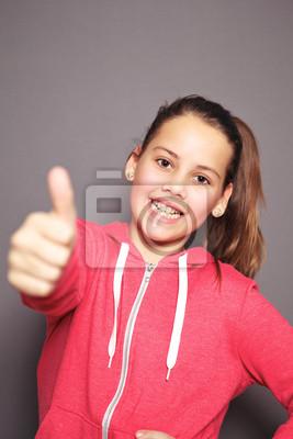 Fröhliche junge Mädchen geben einen Daumen nach oben