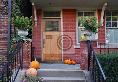 Bild Front porch of older brick house with pumpkins and flower pots
