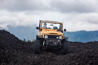 Bild Frontside Blick auf einen kurvenreichen Fahrer in yelow Offroad-Fahrzeug an der Spitze eines Tales mit vulkanischen Felsen und Berge in Bali, Indonesien geparkt