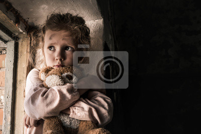 Bild frustrated child holding teddy bear in dirty room, post apocalyptic concept
