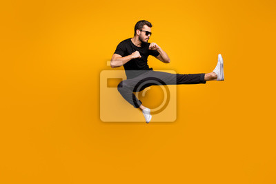 Bild Full length photo of handsome guy jumping high practicing self defense kicking confident facial expression wear sun specs black t-shirt pants isolated yellow color background