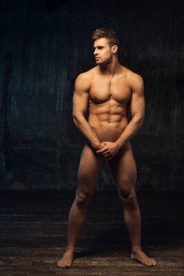 Bild Full length portrait of naked man standing sideways. Muscled male body at dark background. Handsome nude hunk covering himself with hands.