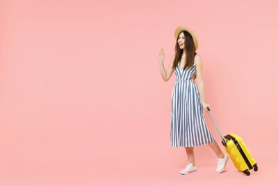Bild Full length traveler tourist woman in summer clothes hat hold yellow valise suitcase waving hand isolated on pastel pink background Passenger travel abroad weekends getaway Air flight journey concept