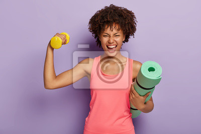 Bild Funny happy dark skinned woman raises hand with dumbbell, shows biceps, holds rolled fitness mat, smiles broadly, wears pink casual vest, isolated over purple background. Fitness training at home