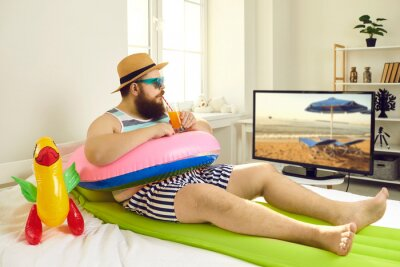 Bild Funny young man with sunglasses and inflatable beach toys sipping cocktail and watching travel show on TV. Concept of canceled summer holiday plans, vacation in lockdown at home or Covid-19 quarantine