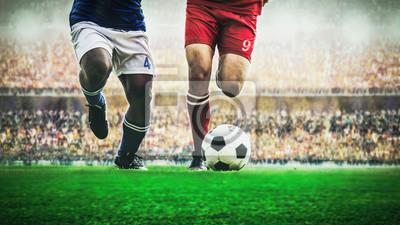 Fußballfußballspieler zwei, der einen Ball während des Spiels im Stadion tröpfelt
