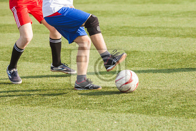 Füße der Spieler im Fußball mit einem Ball close-up.
