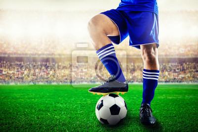 Füße des blauen Mannschaftsfußballspielers auf Fußball für Kick-off im Stadion