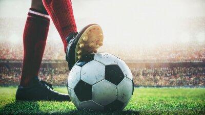 Füße des Fußballspielers treten auf Fußball zum Anpfiff im Stadion