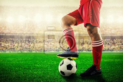 Füße von rotem Team Fußballspieler auf Fußball für Kick-off im Stadion