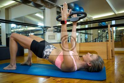 Geeignete Frau, die mit pilates Ring auf Matte trainiert