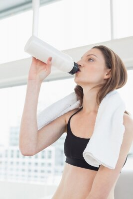 Geeignete Frau mit Tuch um Trinkwasser des Halses im Eignungsstudio