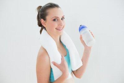 Geeignete Frau mit Wasserflasche gegen Wand