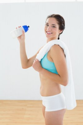 Geeignete lächelnde Frau mit Wasserflasche und -tuch am Eignungsstudio