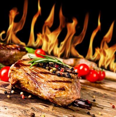 Bild Gegrillte Rindersteaks mit Flammen im Hintergrund