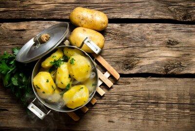 Bild Gekochte Kartoffeln mit Kräutern auf Holztisch. Freier Platz für Text.