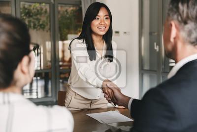 Bild Geschäfts-, Karriere- und Vermittlungskonzept - Bild von zwei Arbeitgebern, die im Büro sitzen und der jungen asiatischen Frau nach erfolgreichen Verhandlungen oder Interviews die Hand schütteln