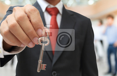 Geschäftsmann zeigt den silbernen Schlüssel zum Erfolg