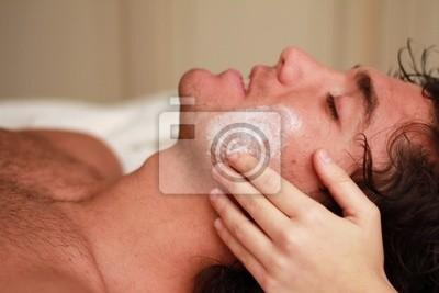 Gesichtsmassage zu einem entspannten junger Mann in der Therme